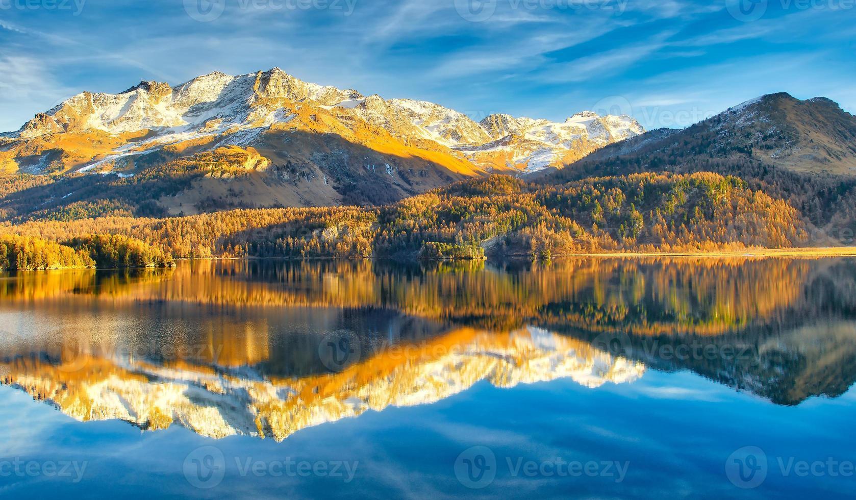 Lago alpino a finales de otoño con reflejos de montañas foto
