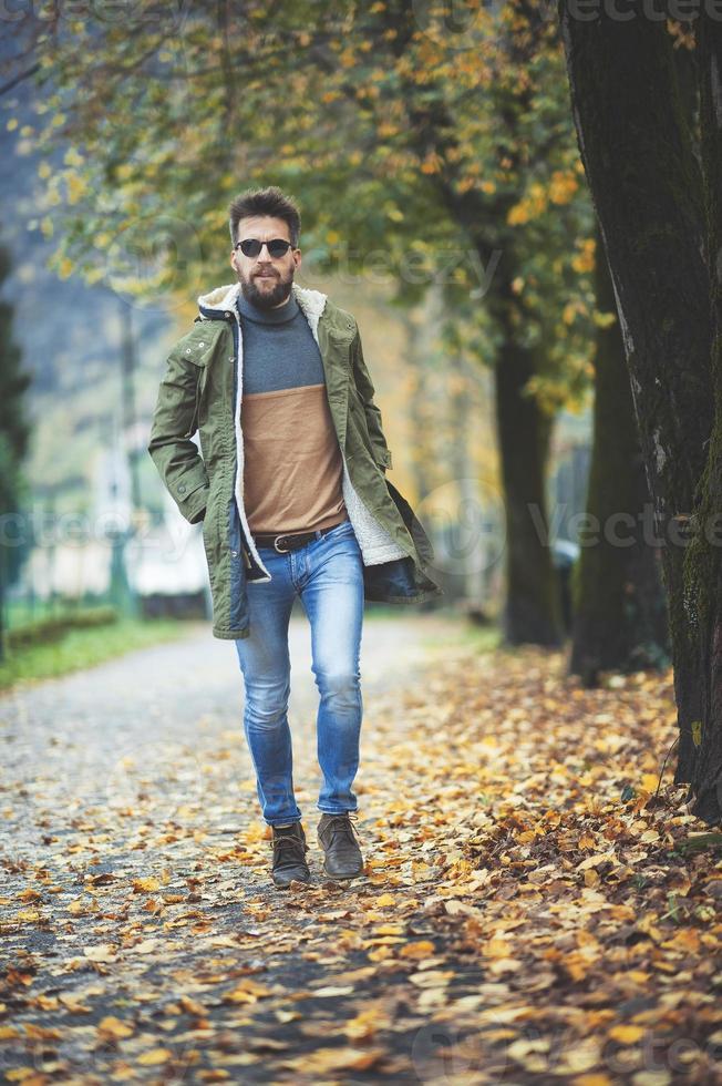 hombre casual estilo hippie caminando entre hojas de otoño foto