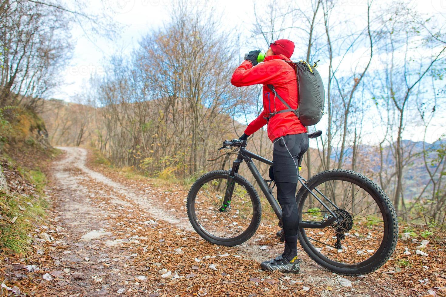 Hombre en bicicleta de montaña descansa y bebe de la cantina. foto