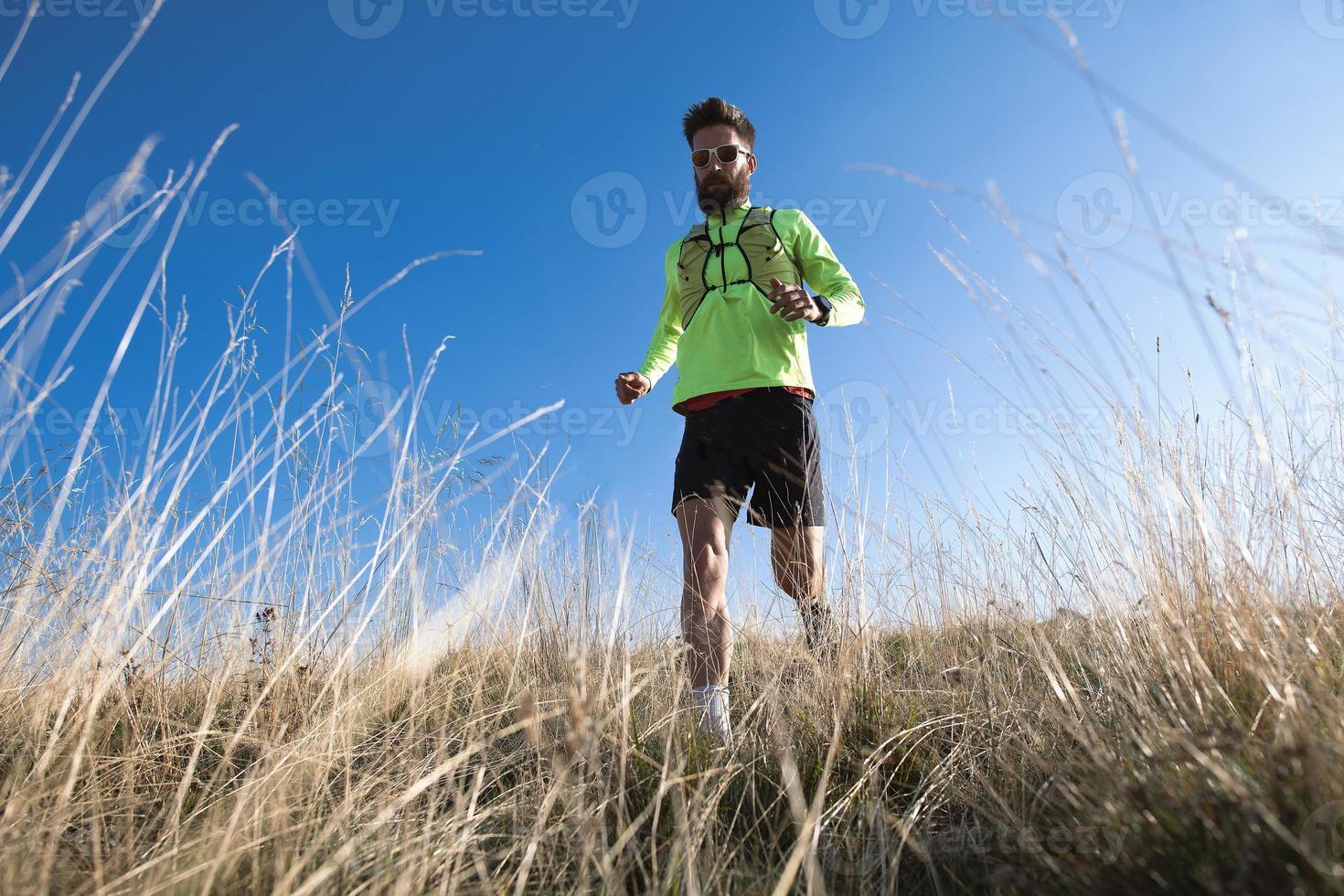 Atleta de montaña cuesta abajo entre los prados de otoño foto