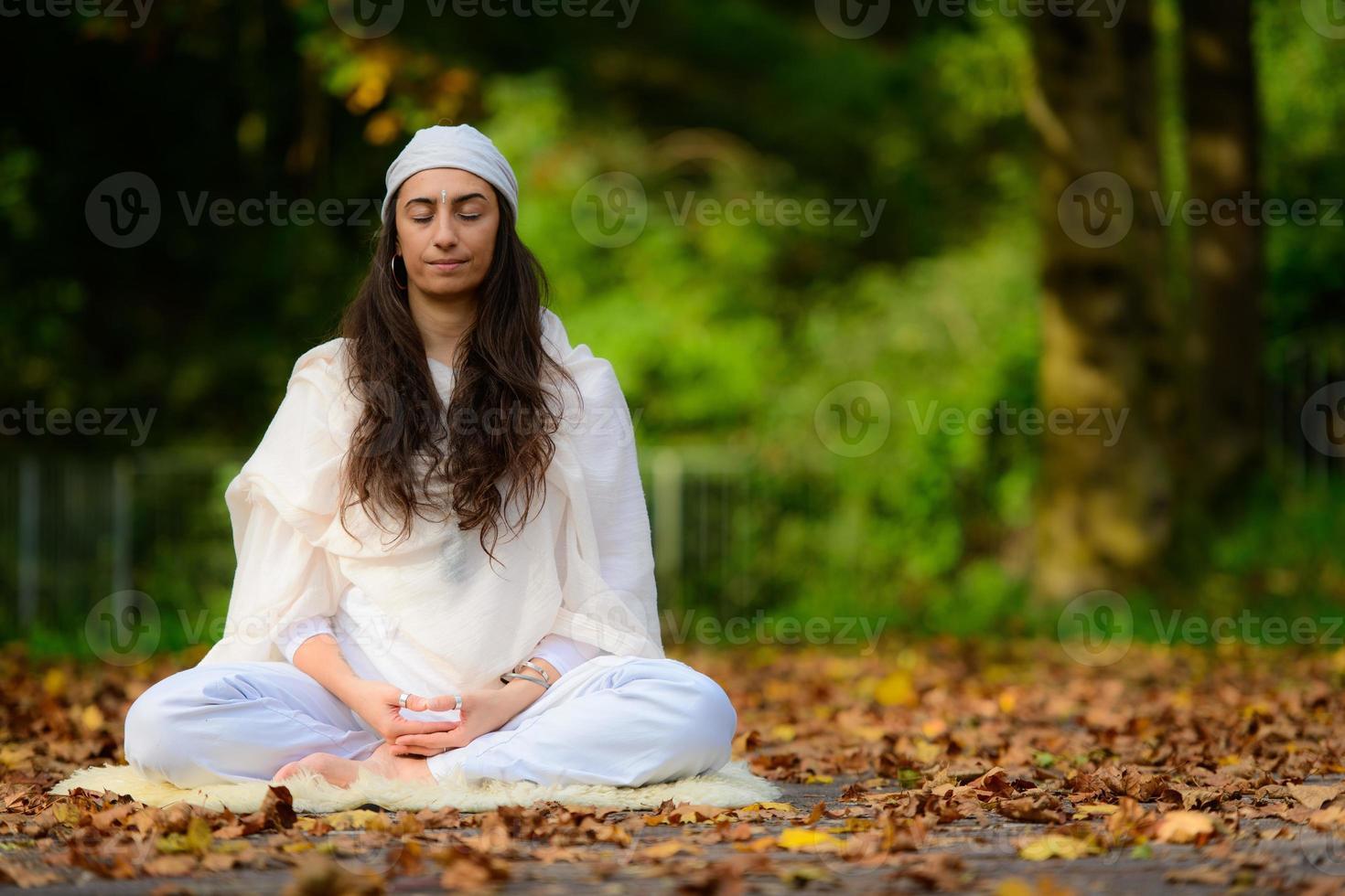 niña practica yoga entre las hojas de otoño foto