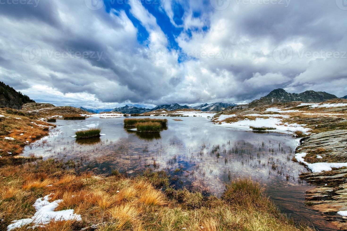 principios de otoño en un pequeño lago en los alpes italianos foto