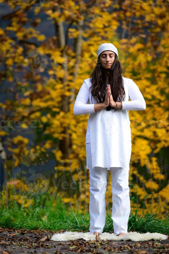 mujer de blanco practica yoga en la naturaleza en otoño foto