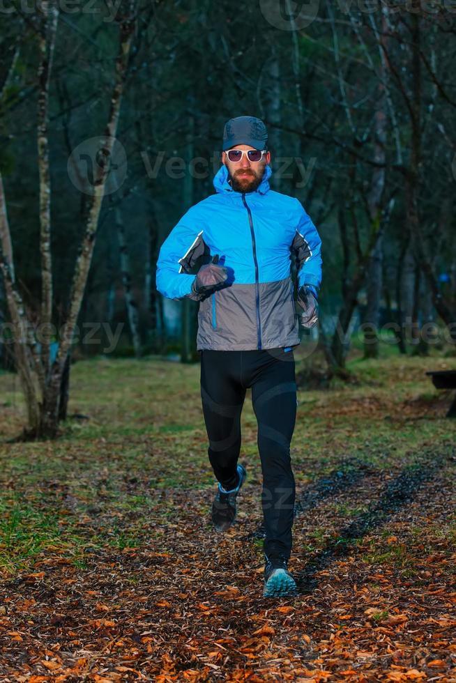 joven atleta durante una carrera en el bosque foto
