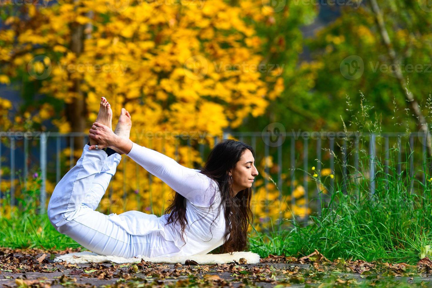 Posición de yoga por una mujer joven en el parque en otoño foto