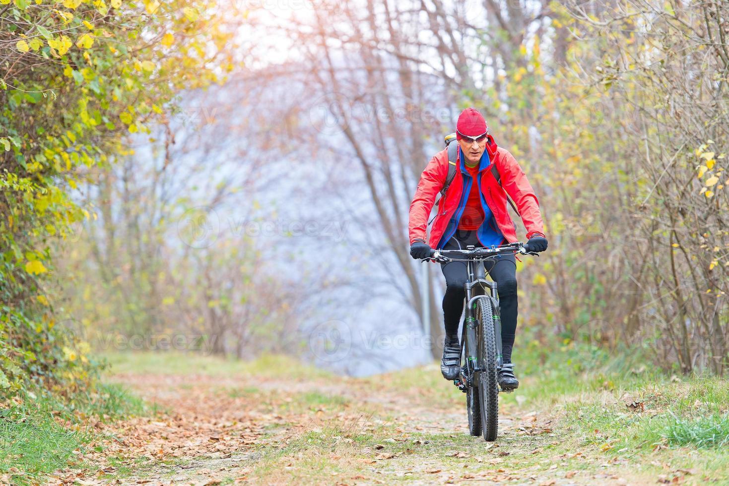 Hombre deportivo se relaja pedaleando una bicicleta de montaña en el bosque foto