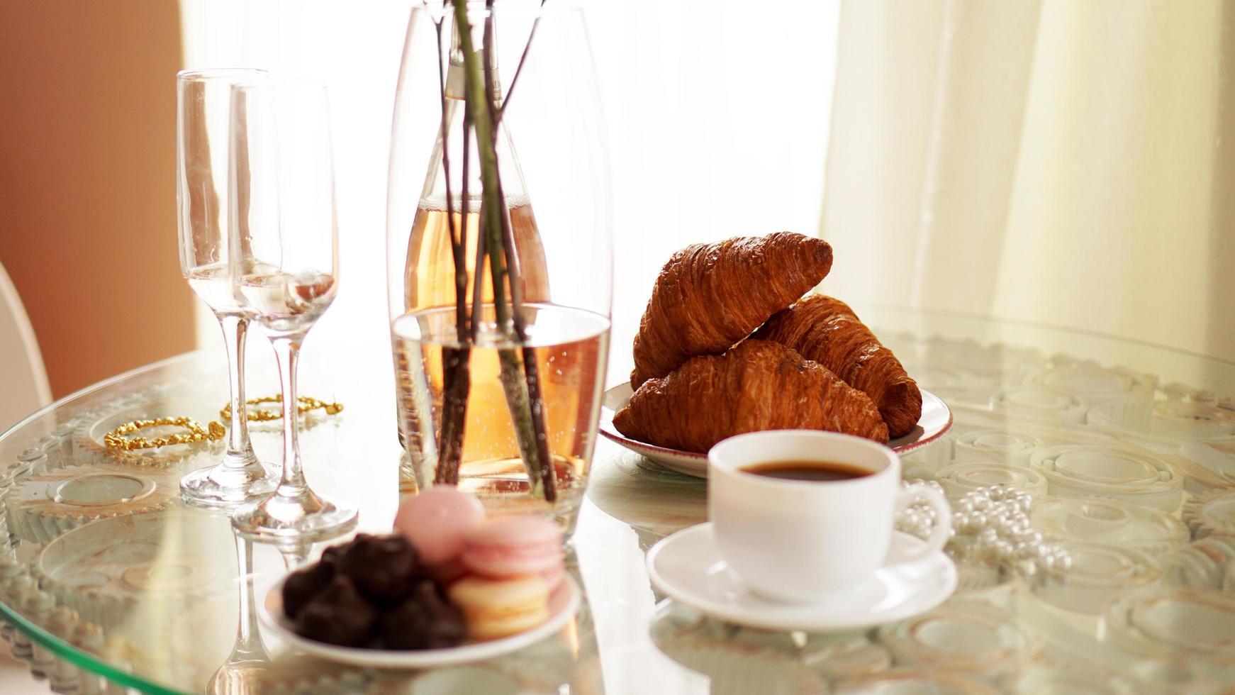 mesa de cristal con una taza de café, croissants dulces foto