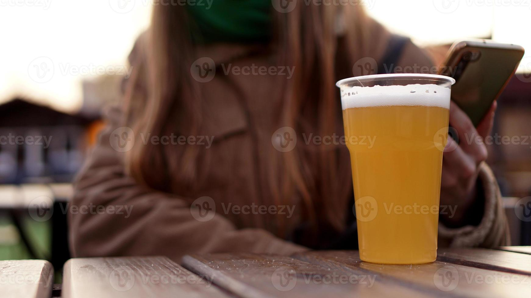 Light beer in a plastic glass. Girl drinking beer at the food court photo