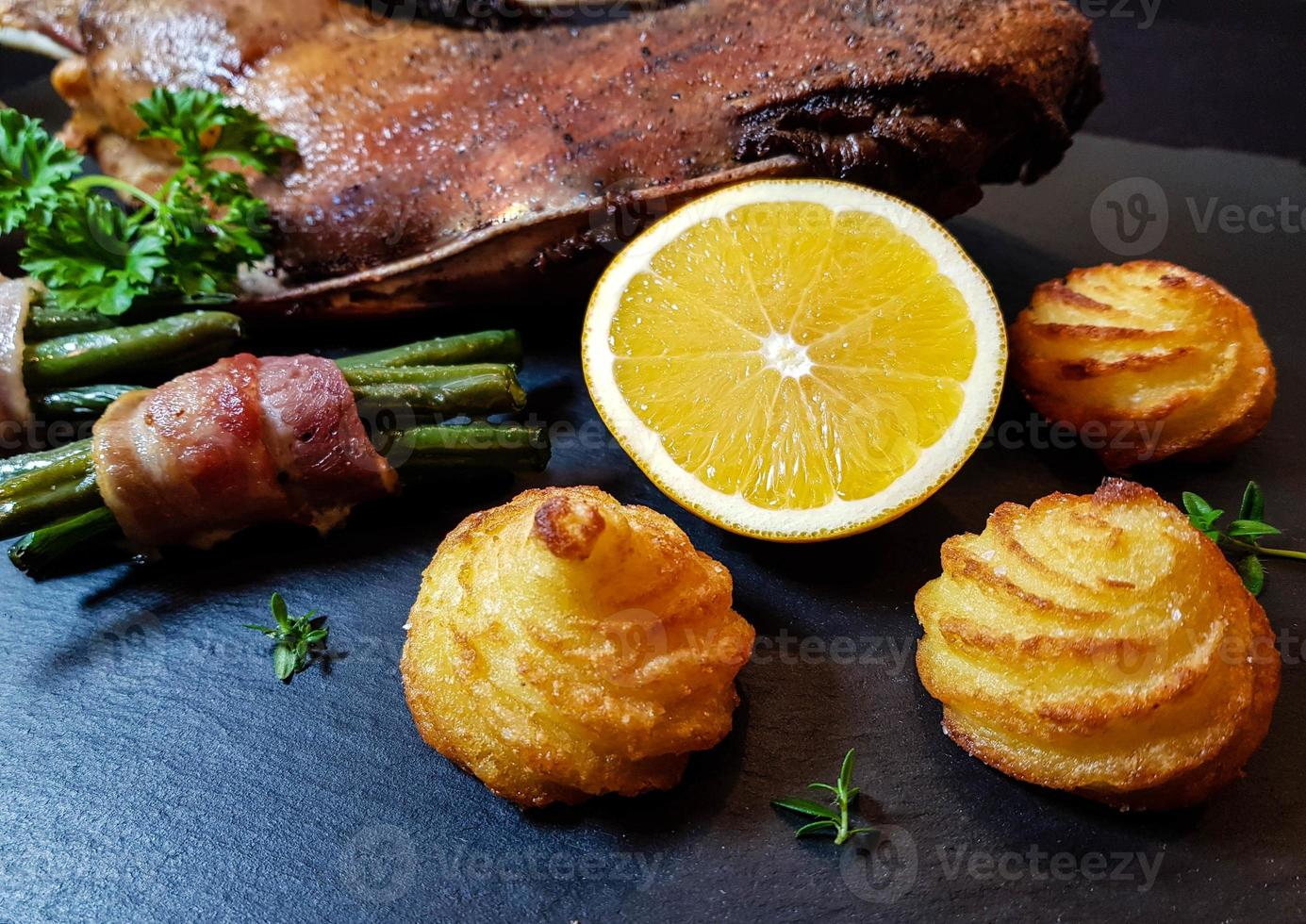 ganso asado con frijoles y patatas duquesa foto