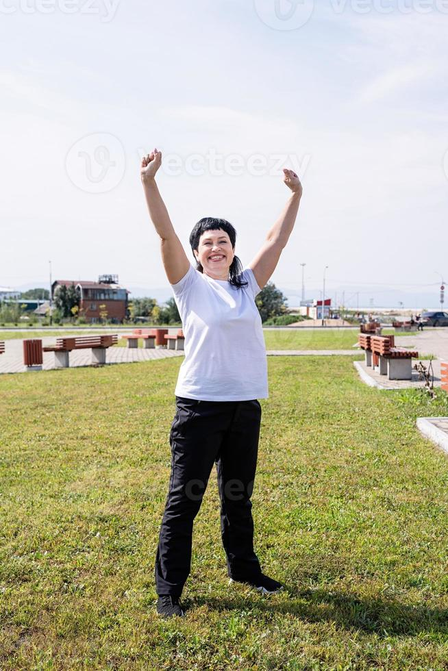 Senior woman in sports clothes exercising in the park standing with up photo
