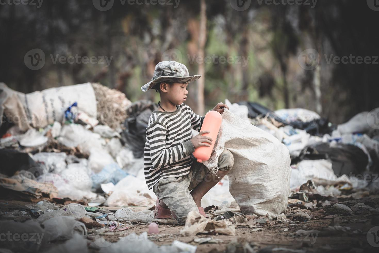 Poor boy collecting garbage in his sack to earn his livelihood. photo