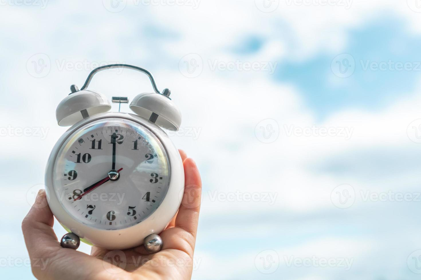 Selective focus of alarm clock with nature bokeh background. photo