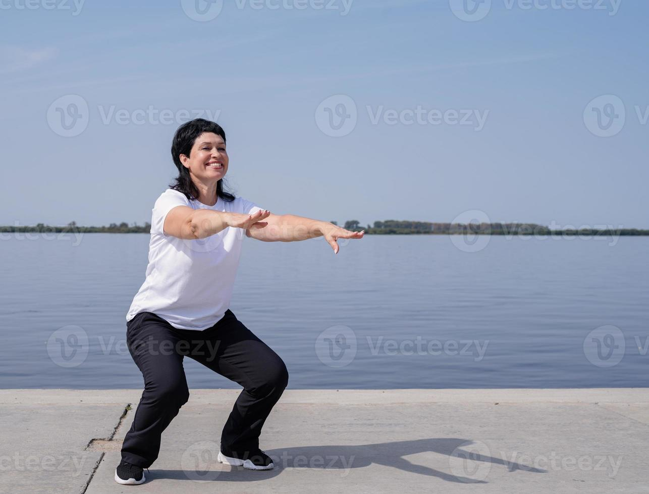 Active and happy senior woman squatting near the riverside photo