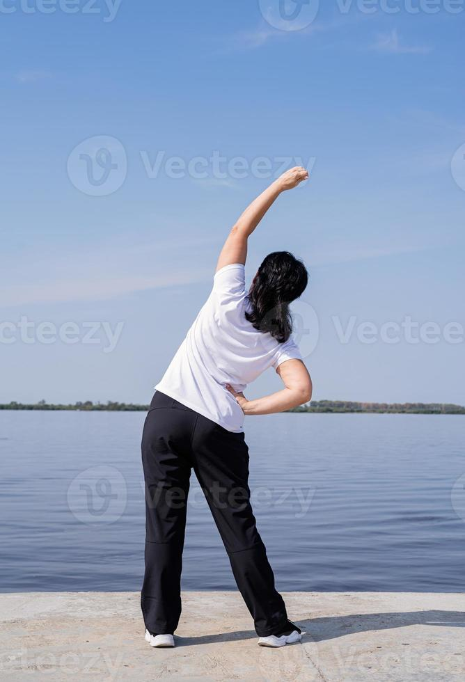Active and happy senior woman doing stretching near the riverside photo