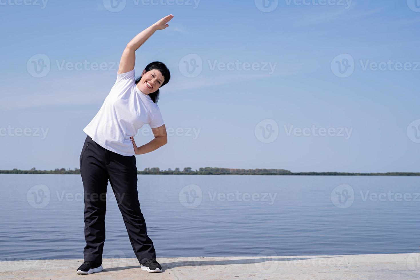 Mujer mayor activa y feliz haciendo estiramientos cerca de la orilla del río foto