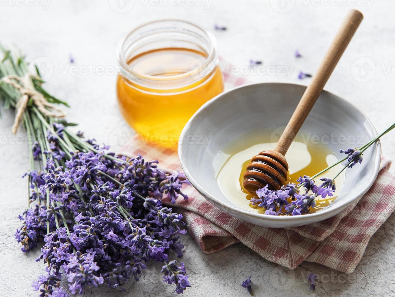 tarro con miel y flores frescas de lavanda foto