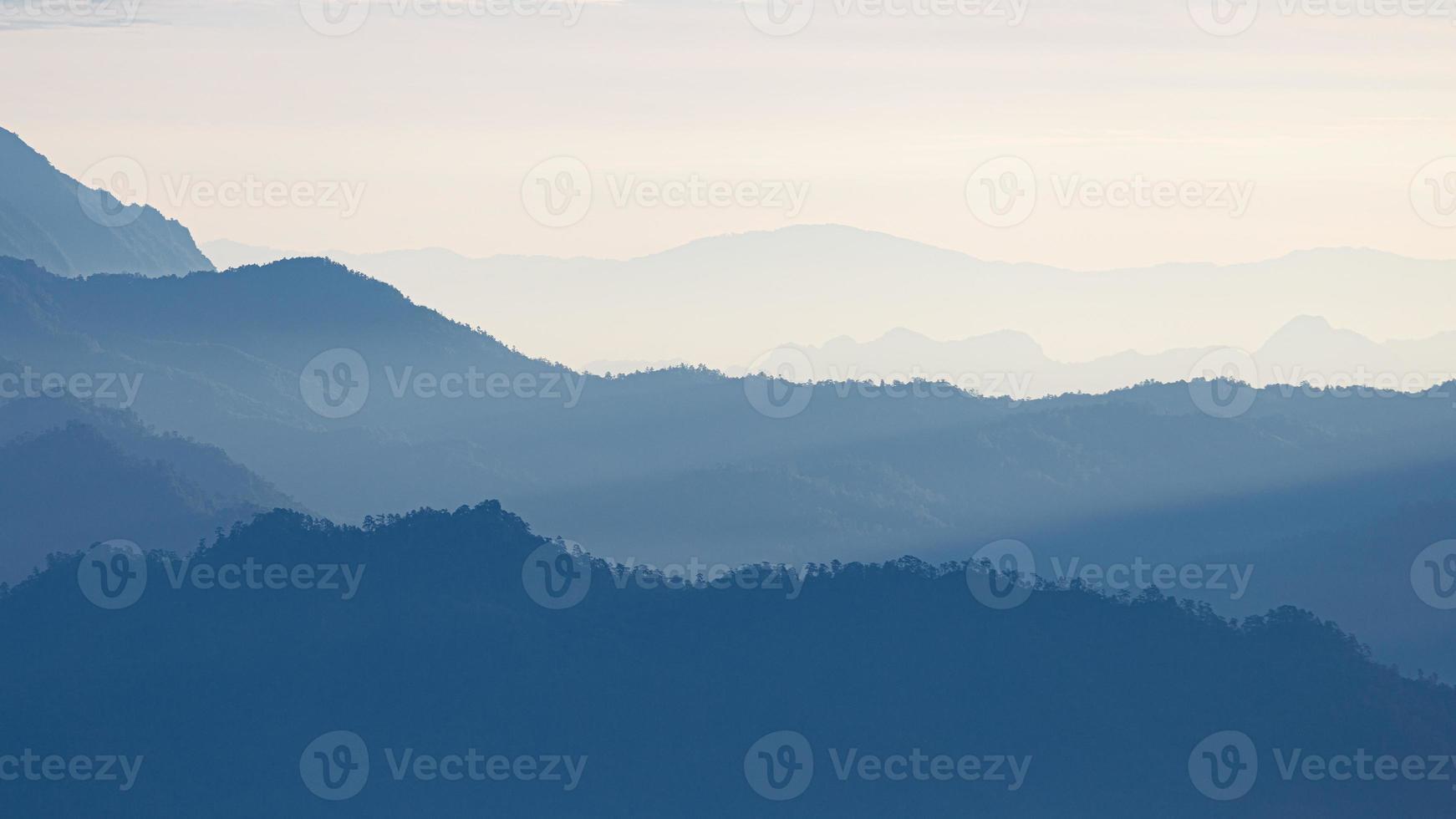 Escena natural de la cordillera azul cubierta por niebla y niebla. foto