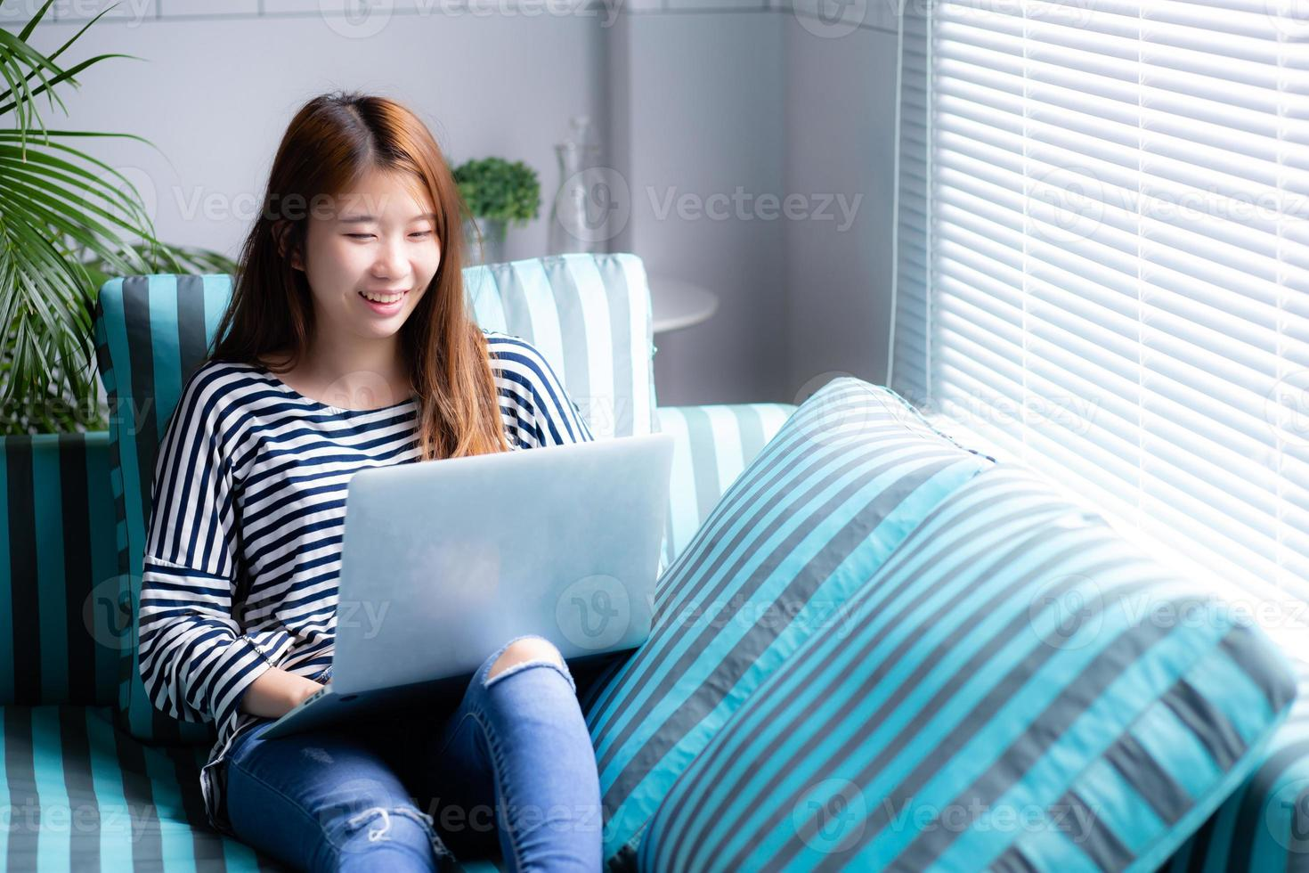 Beautiful of portrait young Asian woman using laptop for leisure on sofa in living room, girl working online with notebook freelance with a happy, communication business concept. photo
