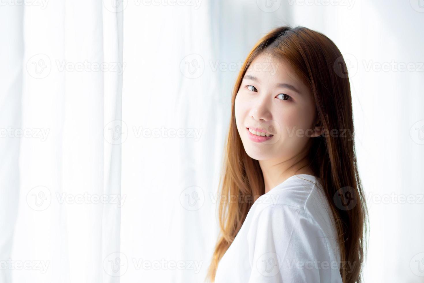 Retrato de una hermosa joven asiática de pie junto a la ventana y sonreír mientras se despierta con el amanecer por la mañana, estilo de vida y concepto de relajación. foto