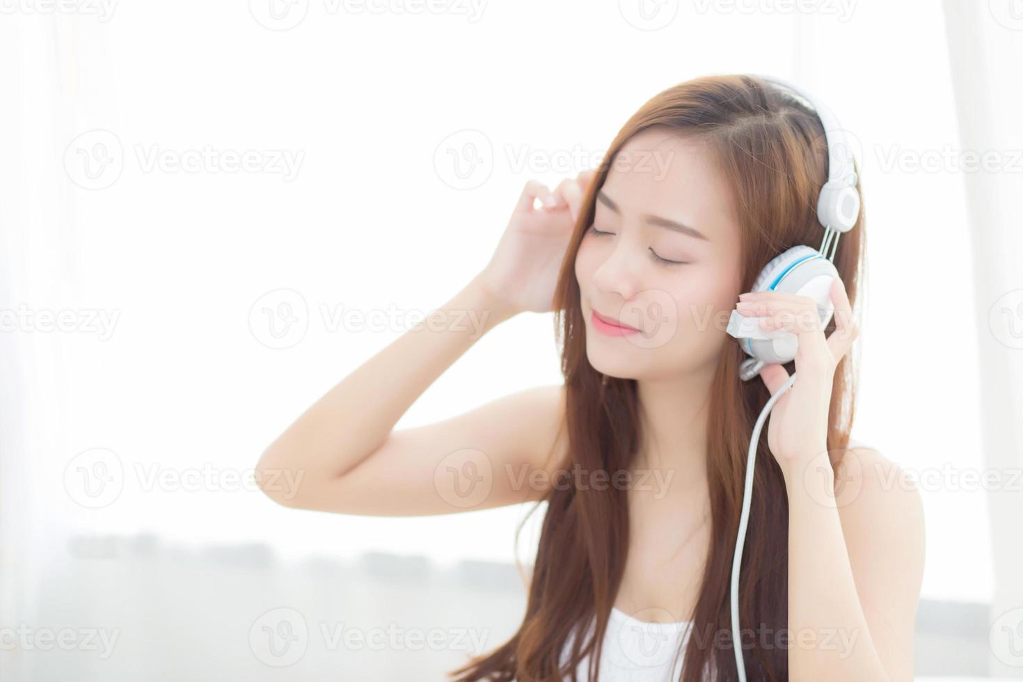 joven asiática disfruta de escuchar música con auriculares. foto