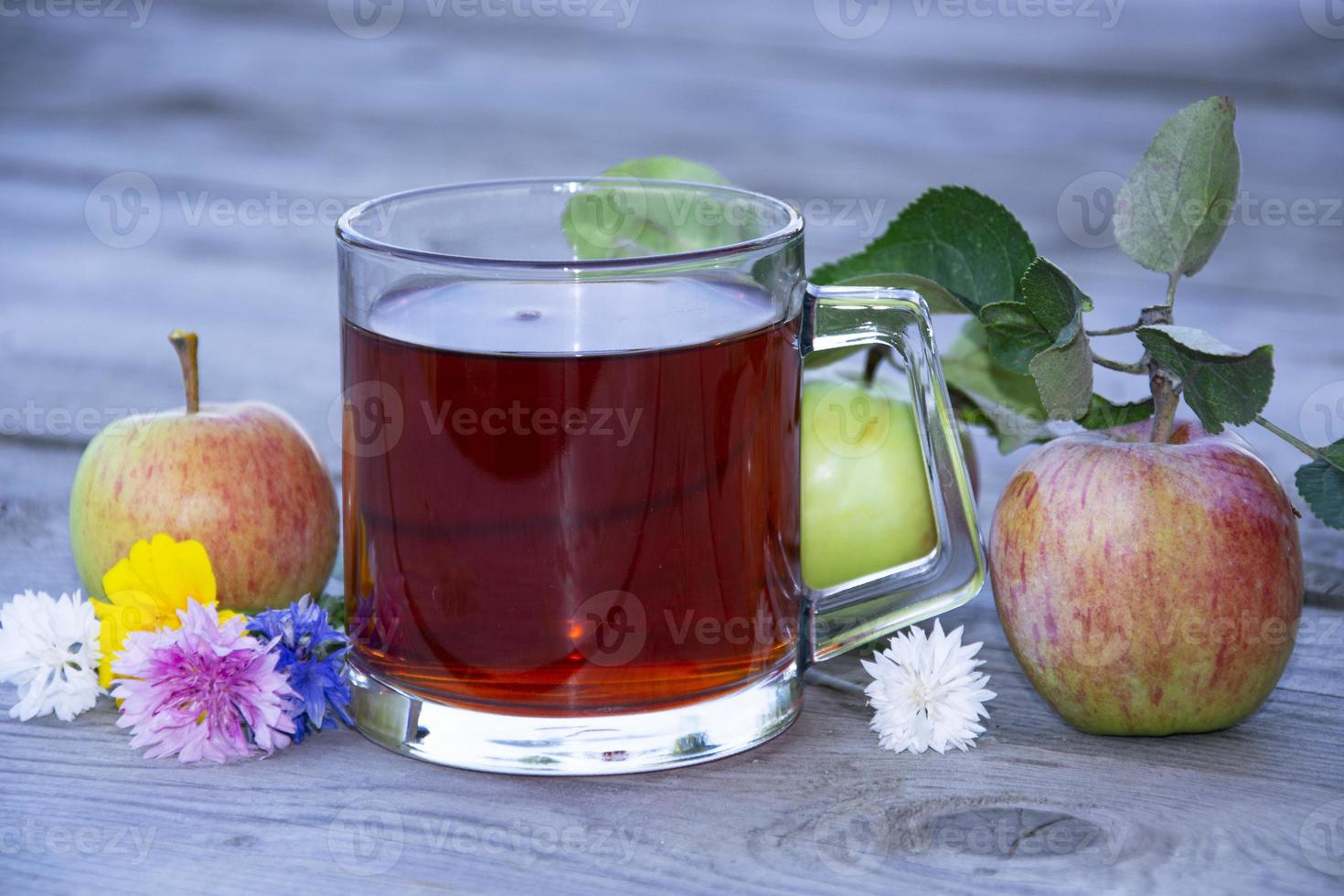 taza con té entre frutas sobre un fondo de madera. foto