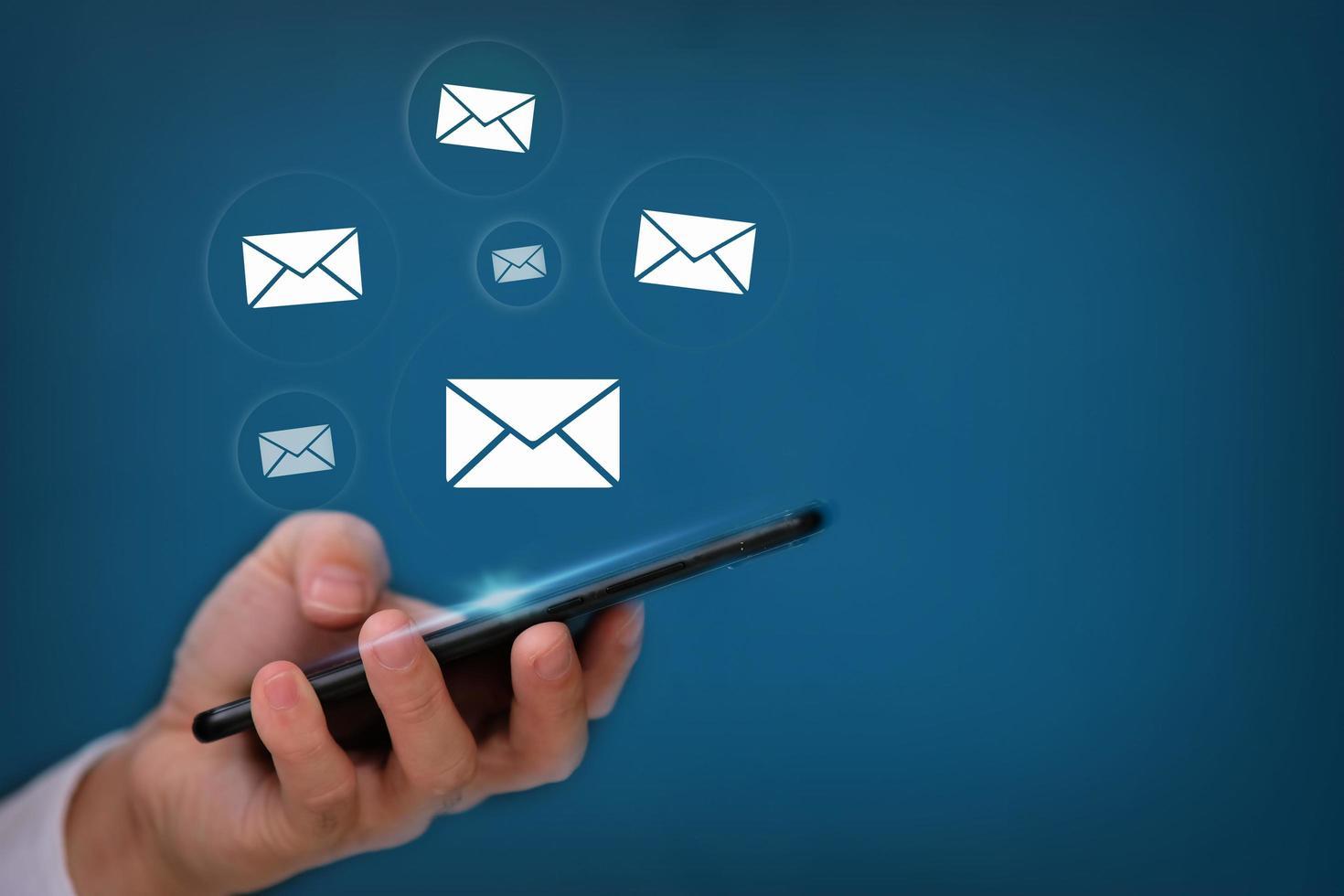 Mano con smartphone con envío de correo electrónico sobre fondo azul. foto