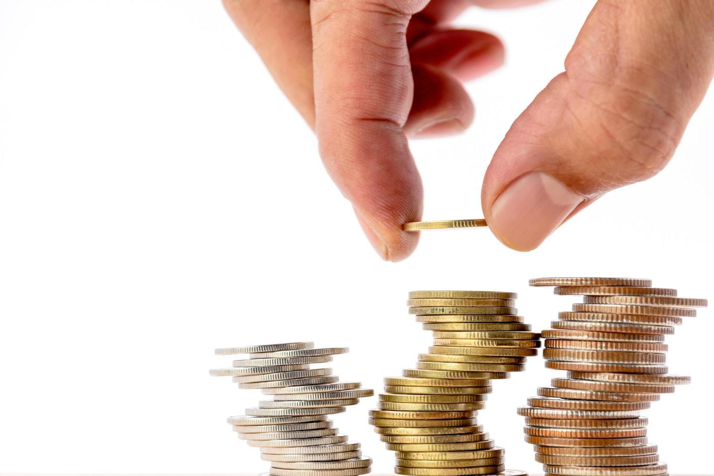 Primer plano de la mano humana poniendo una moneda sobre un montón de monedas. foto