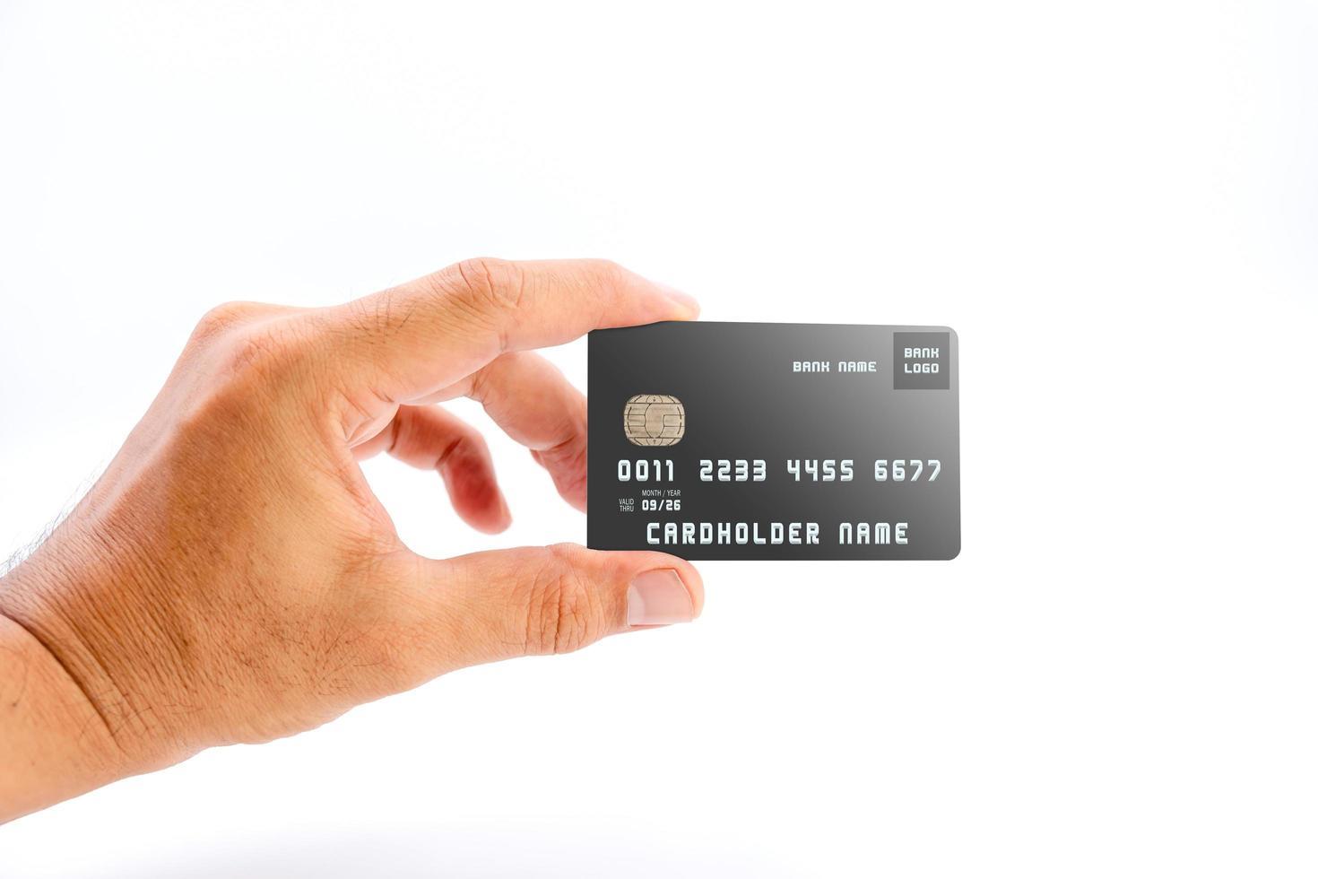 Mano humana sosteniendo tarjeta de crédito bancaria de color negro sobre fondo blanco. foto
