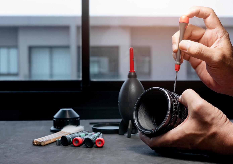 utilizando un destornillador para quitar los tornillos del cuerpo de la lente de una cámara. foto