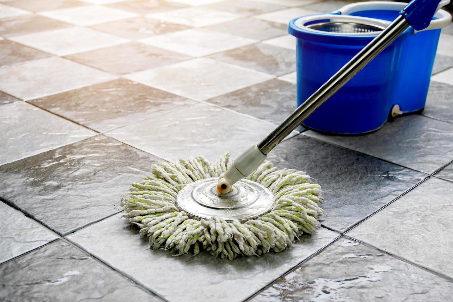 limpie los pisos de baldosas con trapeadores y productos de limpieza para pisos. foto