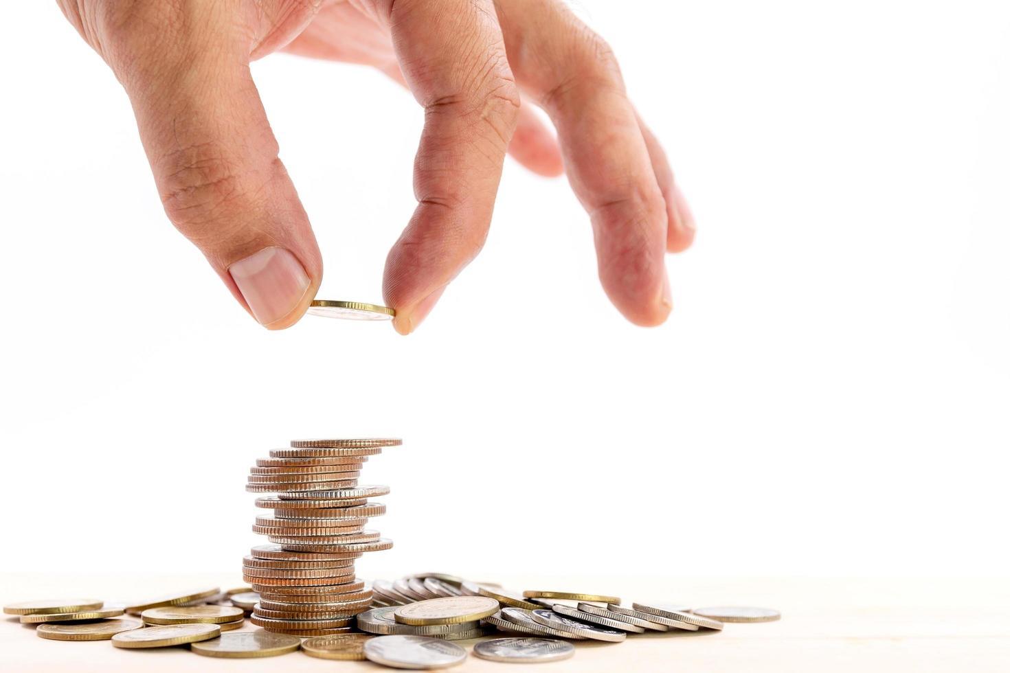 Mano humana poniendo una moneda sobre un montón de monedas sobre fondo blanco. foto