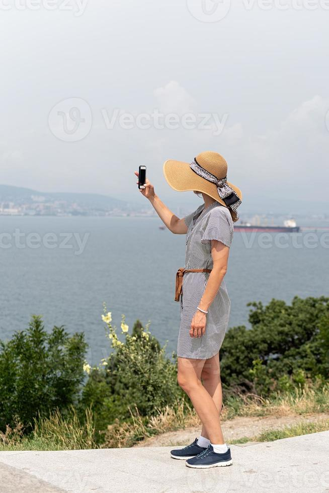 Woman taking picture of the cityscape using mobile phone photo