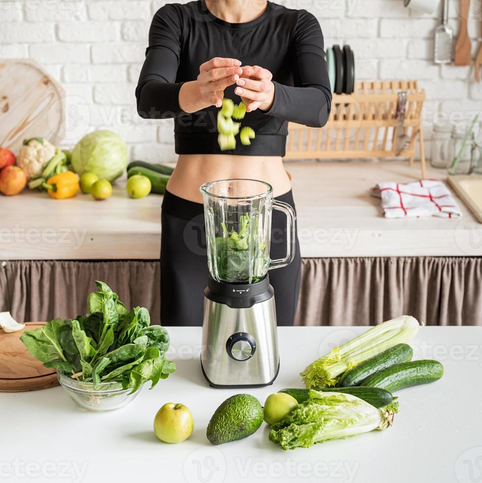 Young blond smiling woman making celery smoothie at home kitchen photo