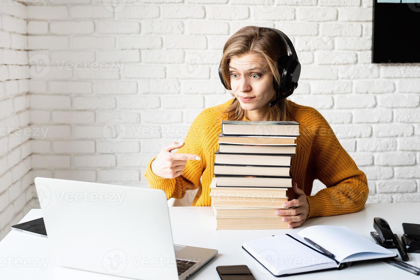 Mujer joven en auriculares negros usando laptop sosteniendo una pila de libros foto