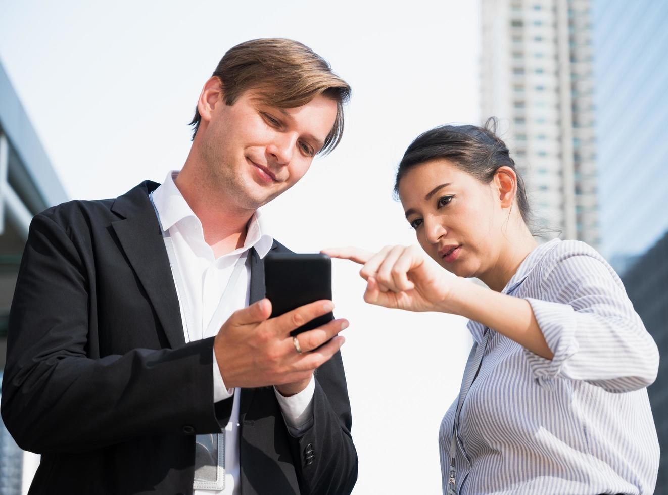 Portrait of businessman and woman looking at phone photo
