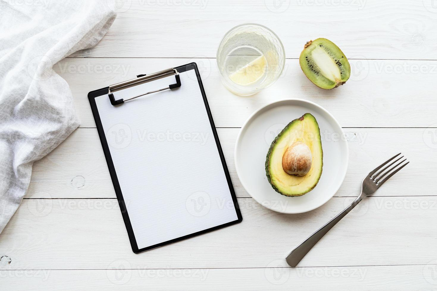Detox plan of avocado and kiwi and blank notepad, top view flat lay photo