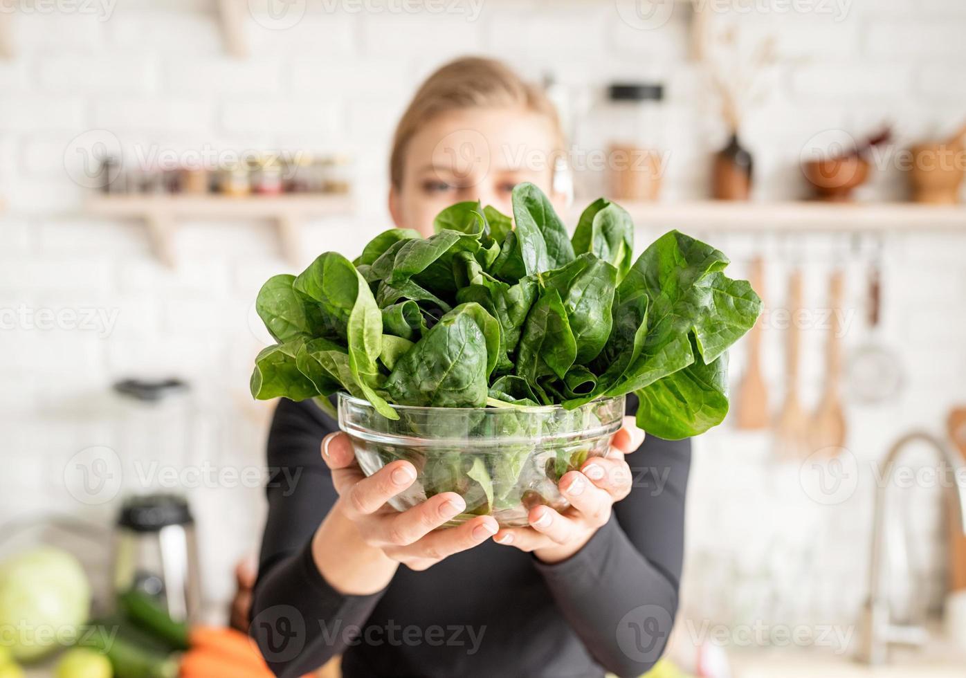 Mujer sosteniendo un plato de espinacas frescas en la cocina foto