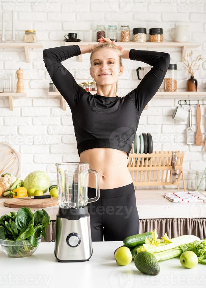 Woman holding a bowl of fresh spinach in the kitchen photo