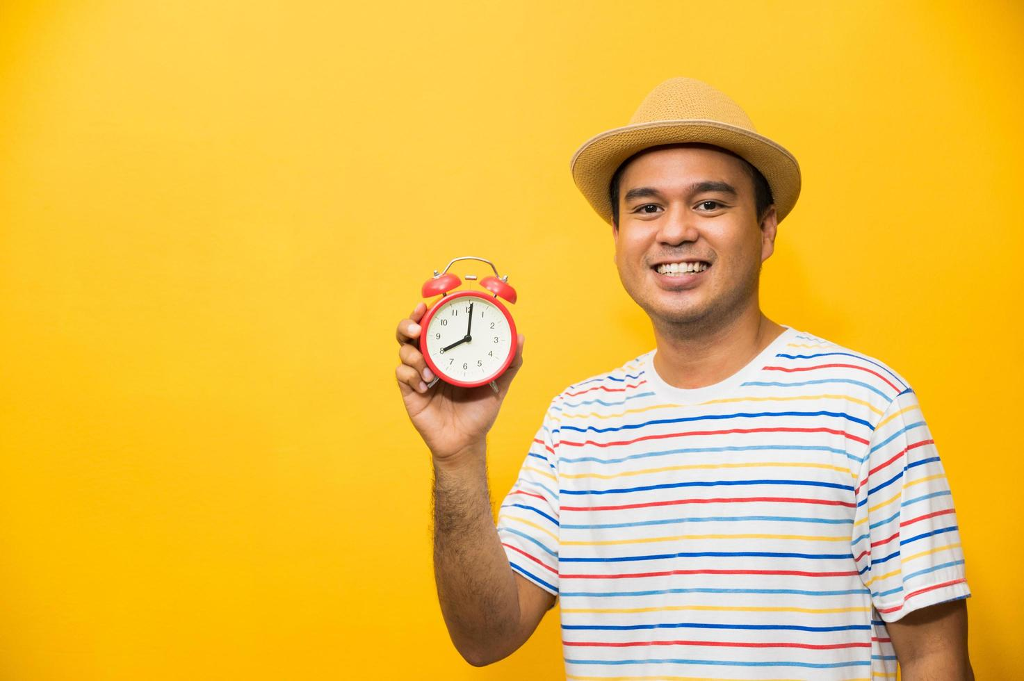 Young asian man holding the alarm clock on yellow isolated background. photo