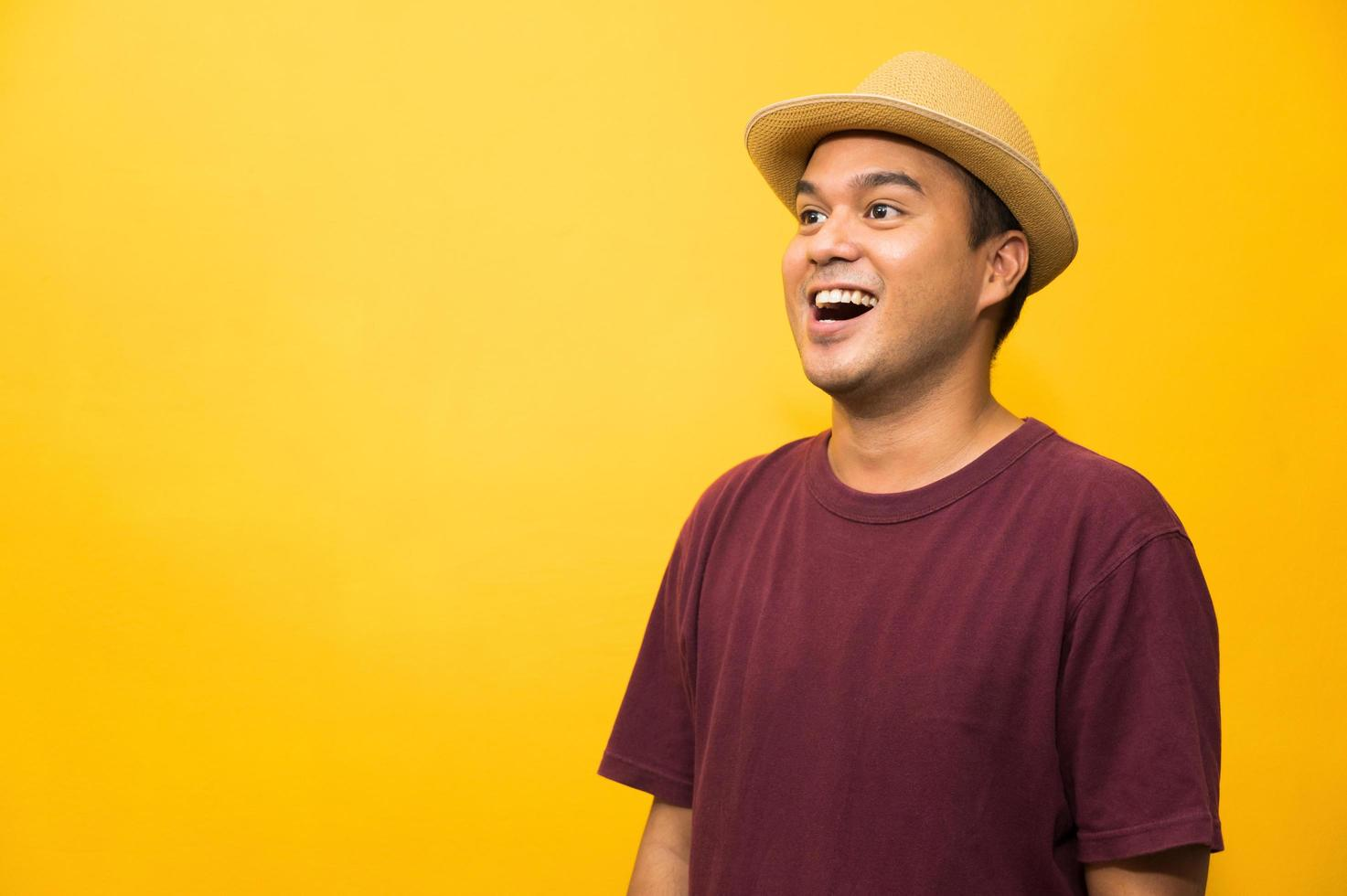 Young asian man looking at copy blank space on yellow background. photo