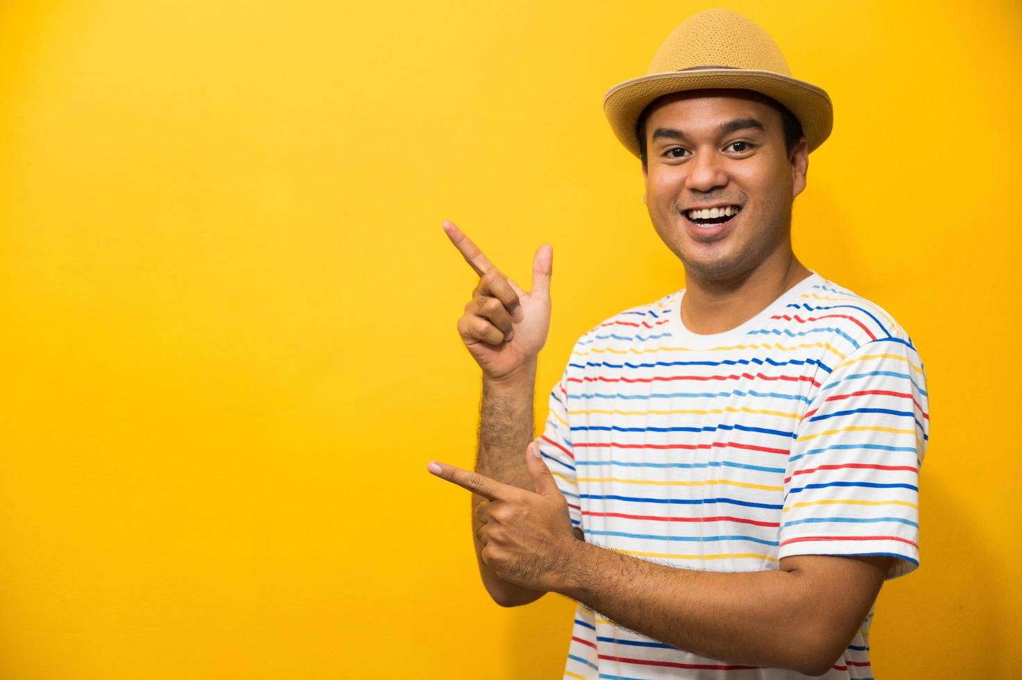 Young happy funny asian man pointing finger on blank space photo