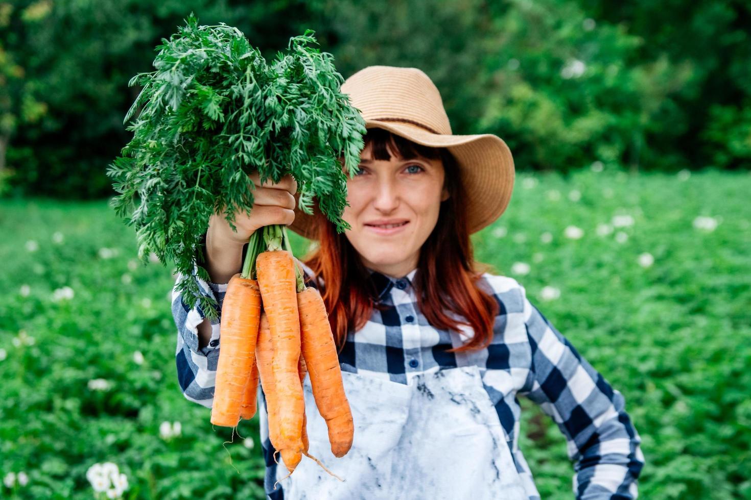 mujer sosteniendo zanahorias foto