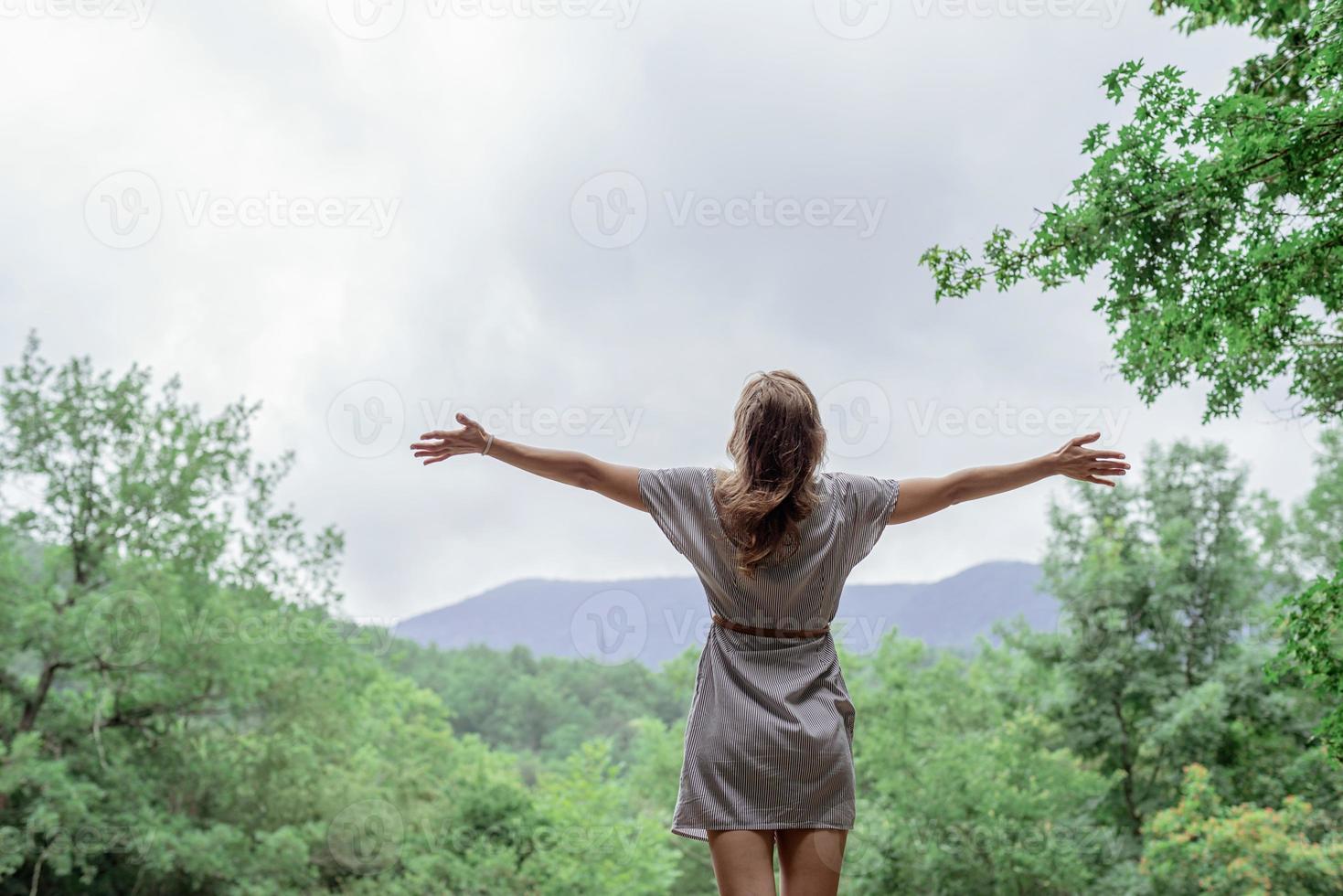 Mujer joven de pie sobre una gran roca en el bosque mirando a otro lado foto