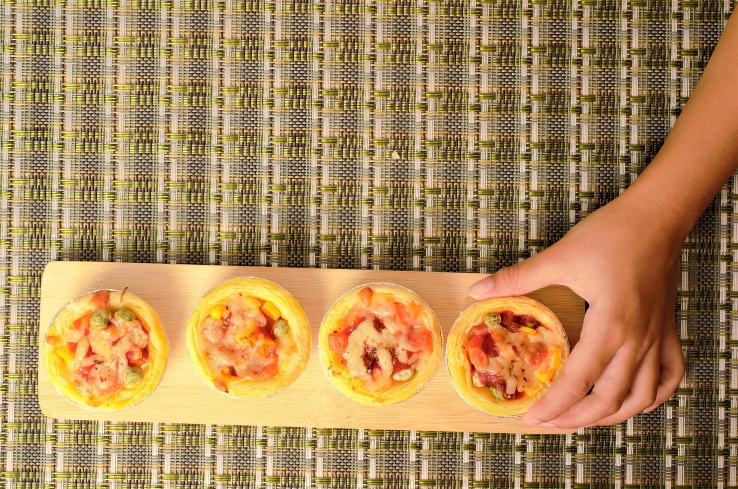 Kids hand touching homemade egg tart pizza backgrounds above photo