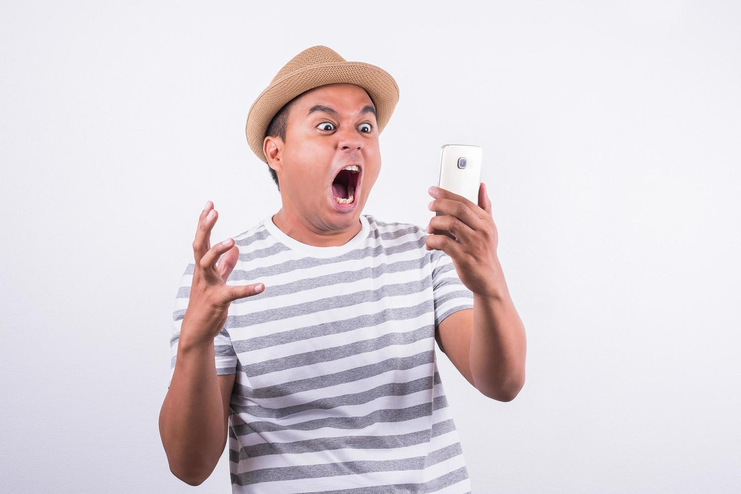 Young asian man looking smartphone and feels shock photo