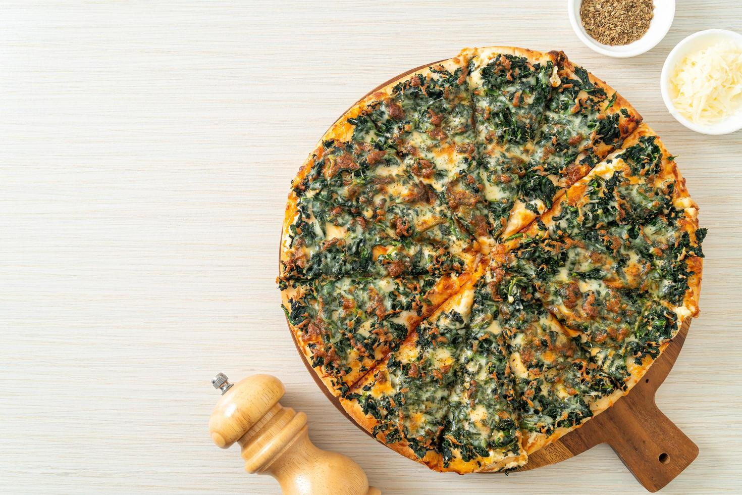 Spinach and cheese pizza on wood tray photo
