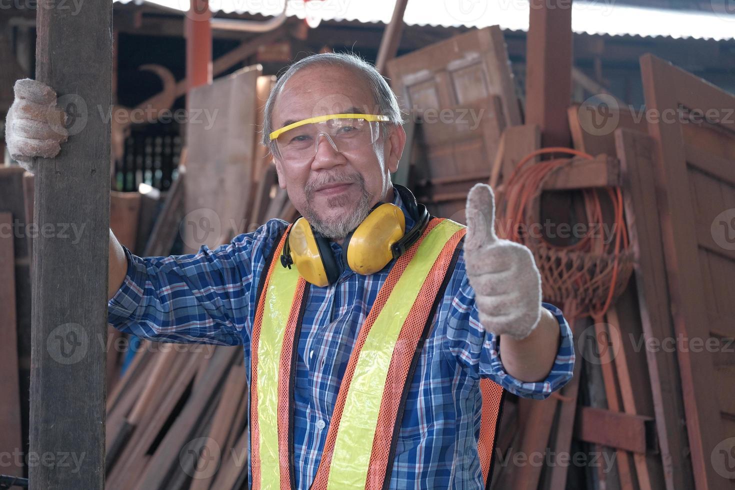 Carpintero masculino senior trabajando y pulgar hacia arriba en la fábrica de aserraderos de madera. foto