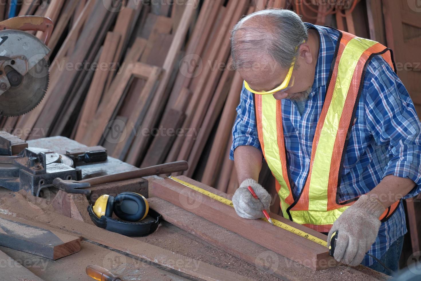 Viejo carpintero asiático que trabaja en una fábrica de carpintería. foto