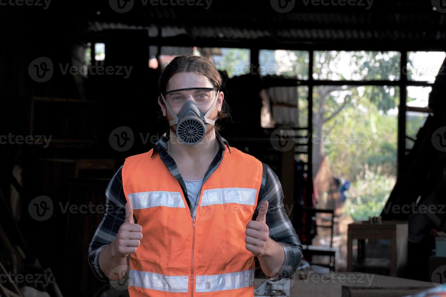 joven carpintero pulgar hacia arriba y sonreír en la fábrica de madera. foto