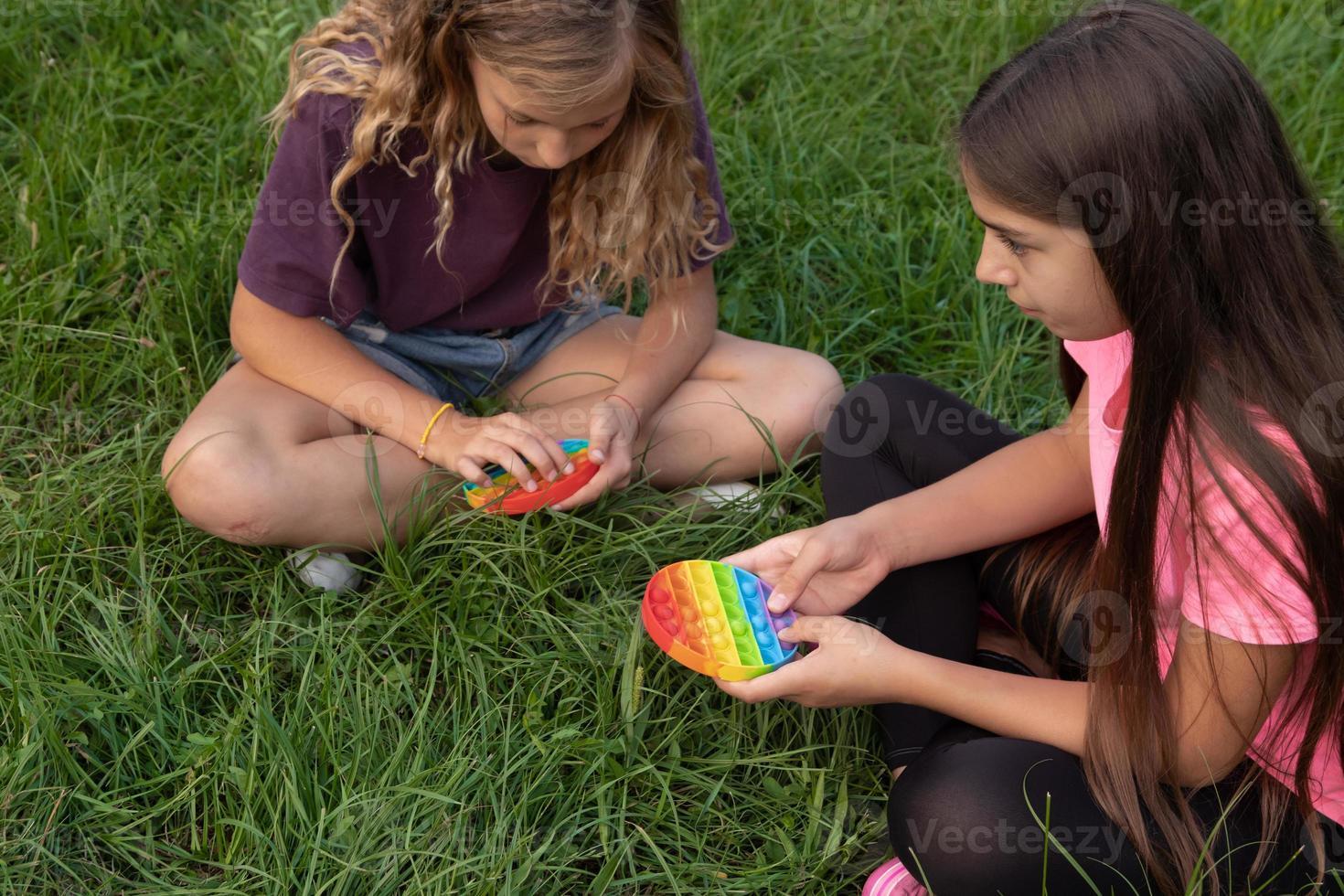 las niñas juegan al aire libre el popular juguete pop-it con toque de silicona colorido foto